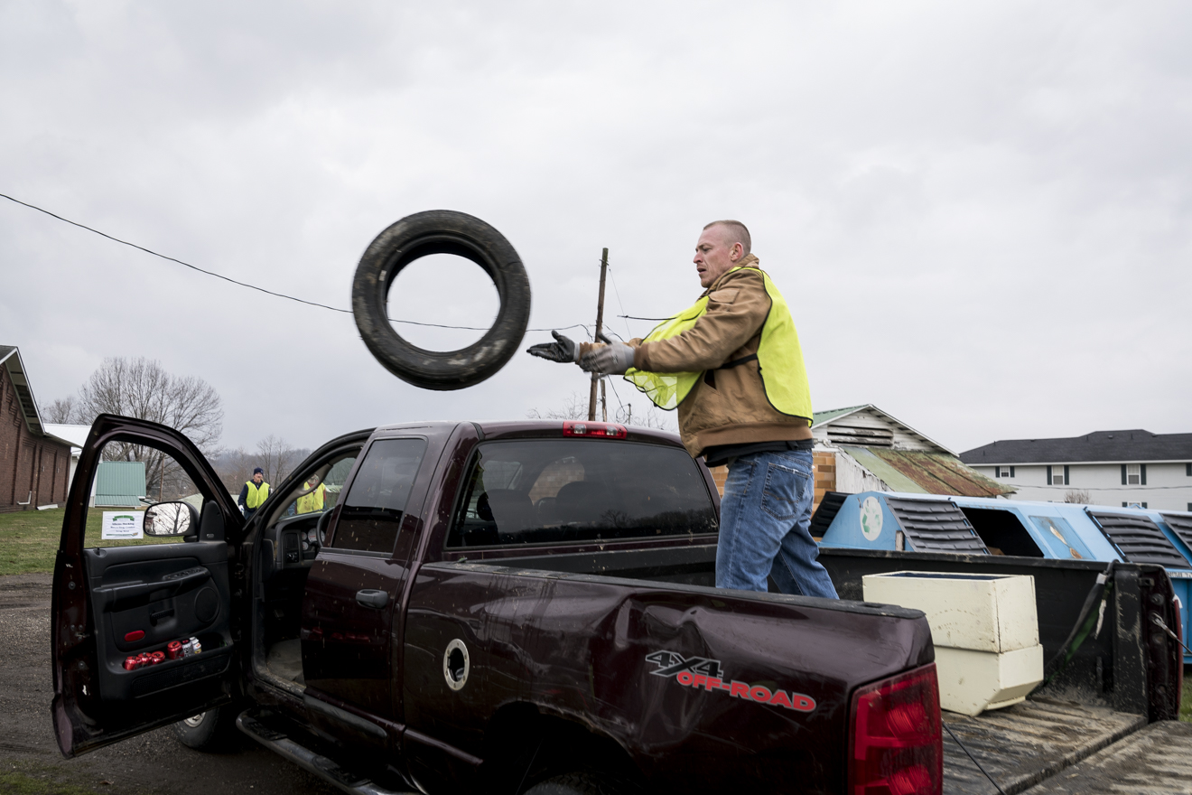 A volunteer from SEPTA Correctional Facility at the Recycle Mania event held at the Athens County Fair Grounds throws tires out of a car to be collected and recycled.