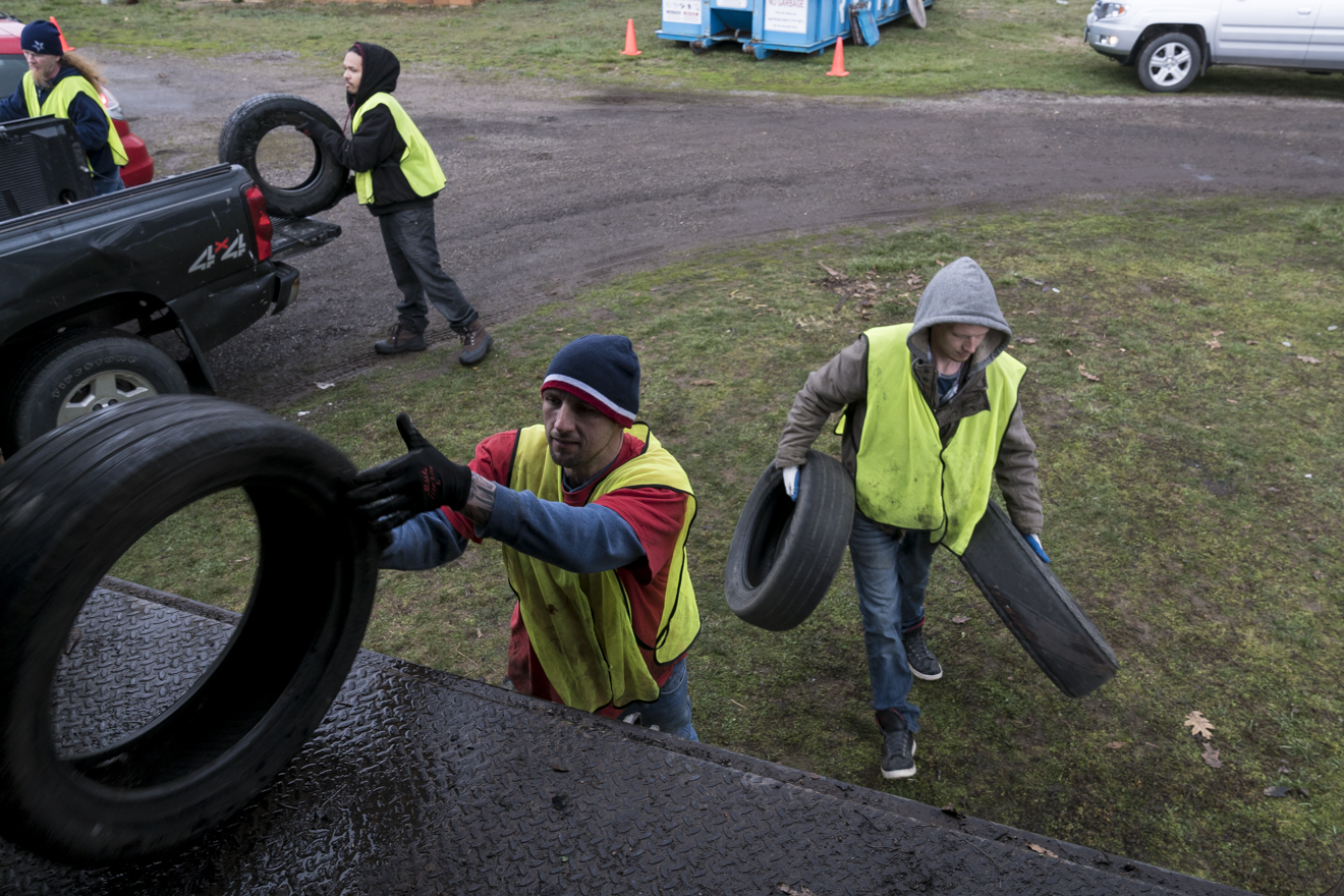 Volunteers from SEPTA Correctional Facility at the Recycle Mania event held at the Athens County Fair Grounds collect tires and throw them into the bed of a truck to be recycled.