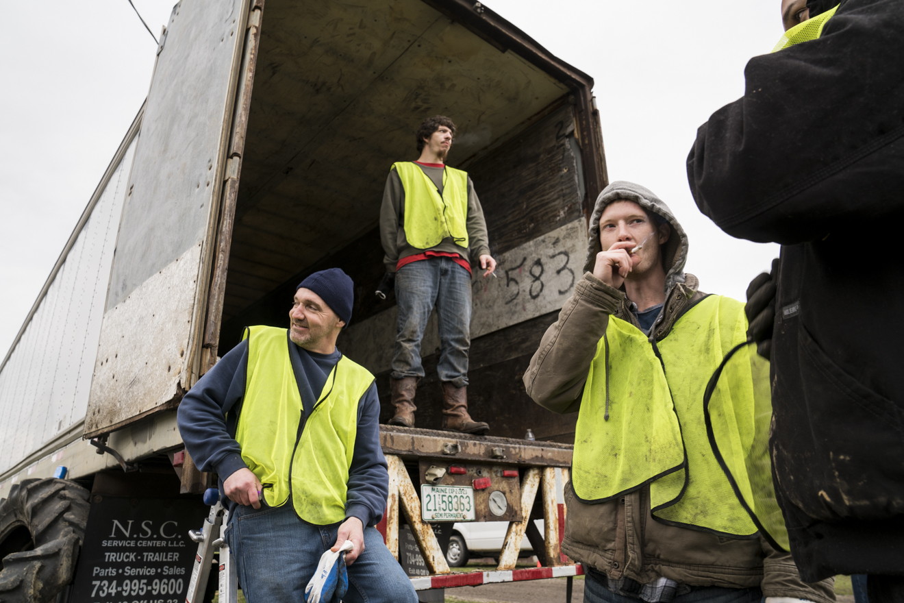 Volunteers from SEPTA Correctional Facility take a smoke break while waiting for more tires to load into the bed of the truck.