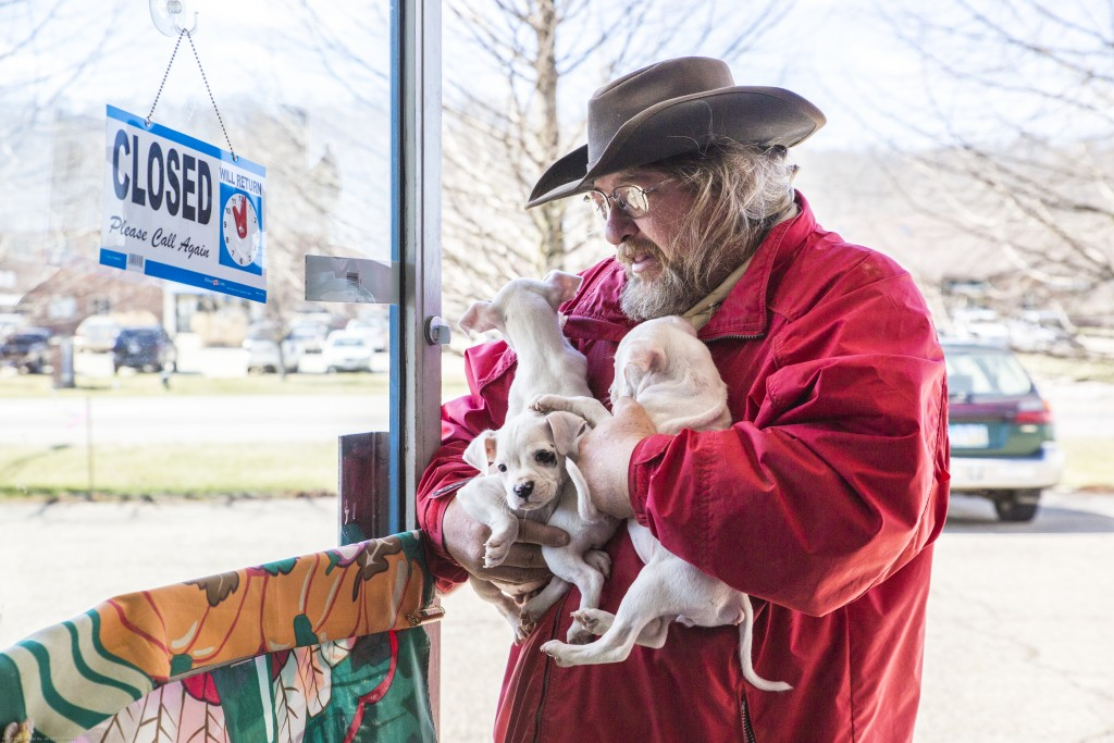 Wayne Boyd, the founder of the New Beginnings Animal Center, takes in three puppies from Hanna Rose in Wags & Whiskers Curiosity Thrift Shoppe on March 13, 2017 in Athens, Ohio. The New Beginnings Animal Center is a licensed non-profit organization to find forever homes for the mistreated, neglected and homeless dogs of Athens and surrounding counties. (Wangyuxuan Xu/WOUB)