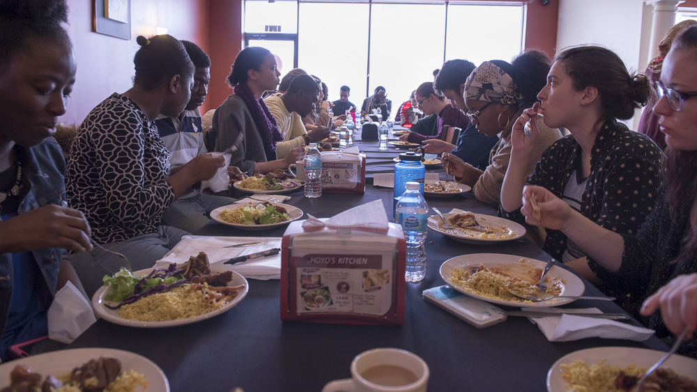Ohio University students eat a traditional Somali meal at Hoyo's Kitchen in Columbus, Ohio on March 18, 2017. (Camille Fine/WOUB)