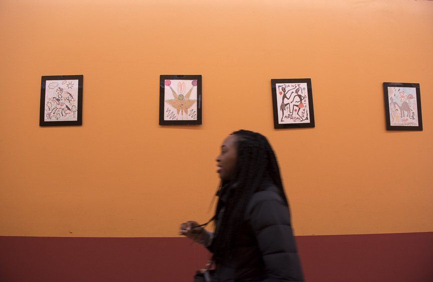 Brooke Siggers, a junior at Ohio University studying Global Studies, walks by a group of paintings at the Global Mall in Columbus, Ohio on March 18, 2017. (Camille Fine/WOUB)