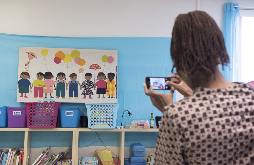Professor Edna Wangui of Ohio University takes a picture of children's artwork in the Focus Learning Acadamy for Somali immigrants on March 18, 2017 in Columbus, Ohio. (Camille Fine/WOUB)