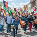 Marchers carrying various international flags walk up coart street during the international street fair parade. Photo by: Ross Brinkerhoff.