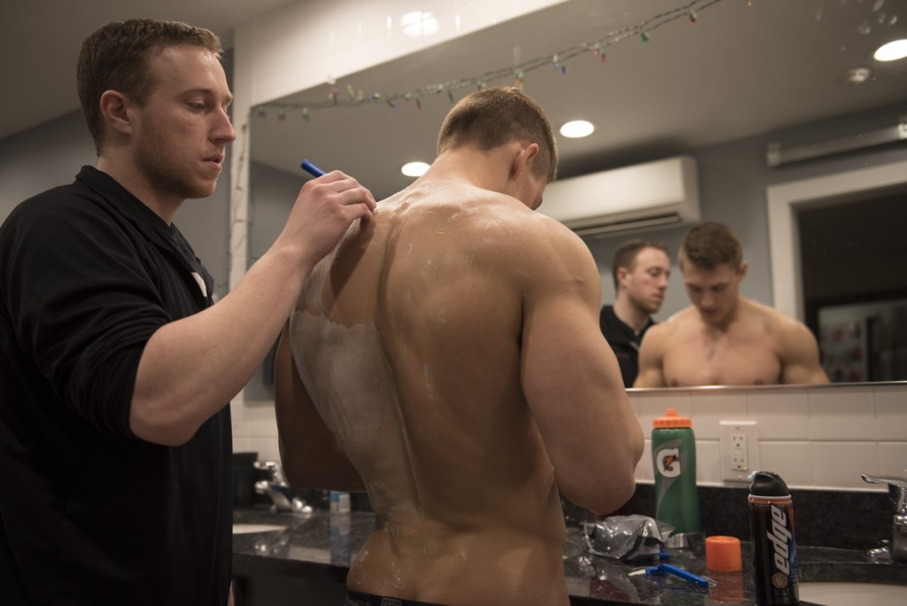 "Nick's fraternity brother Jeremy Ledonne helps shave his back before he gets his spray tan. ""Nick has an innate ability of drawing others in and motivating them with his love and excitement for fitness. People who have little knowledge or experience with training often seek out Nick's advice due to his friendly and approachable demeanor,"" said Ledonne. (Robert McGraw/WOUB)"