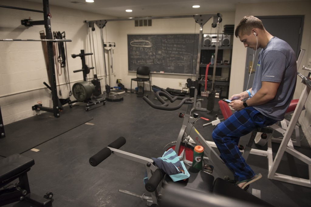Nick kickstarts his metabolism every morning on a stationary bike in the gym located in the basement of his fraternity house. (Robert McGraw/WOUB)