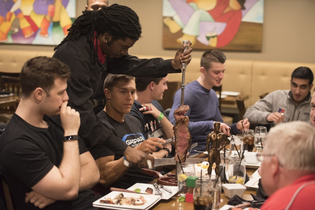After competing in the men's physique finals, Nick enjoys a hard-earned feast with his close friends and family who have supported him throughout his fitness journey. (Robert McGraw/WOUB)