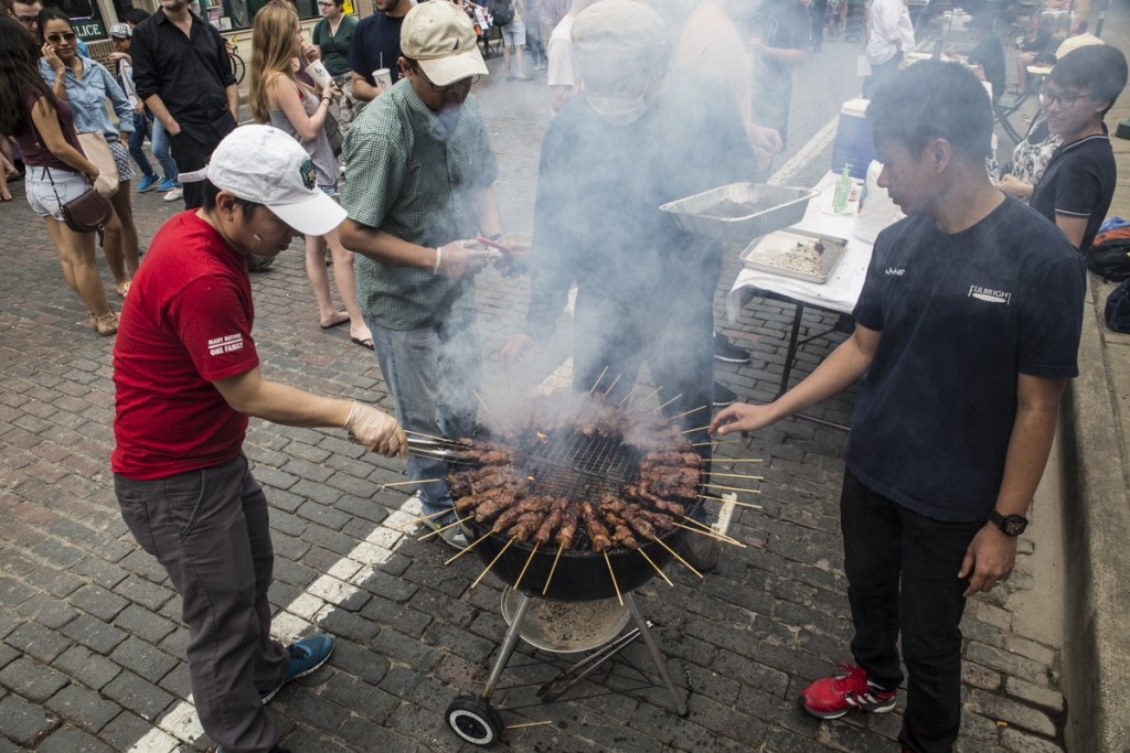 Staffs of Javanese Student Association roasts meat on the International Week Street Fair on the Court Street in Athens, Ohio, on April. 15, 2017. (Wangyuxuan Xu/WOUB)