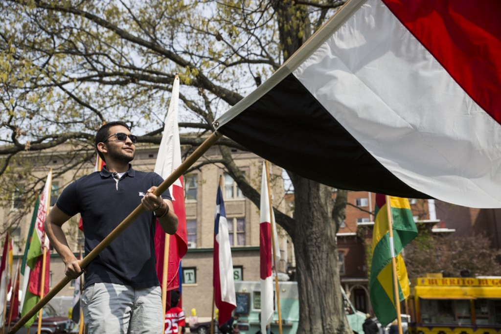 Karin Elmasty, an international student comes from Yamen, raises his country's flag on the International Week Street Fair near the college gate in Athens, Ohio, on April. 15, 2017. (Wangyuxuan Xu/WOUB)