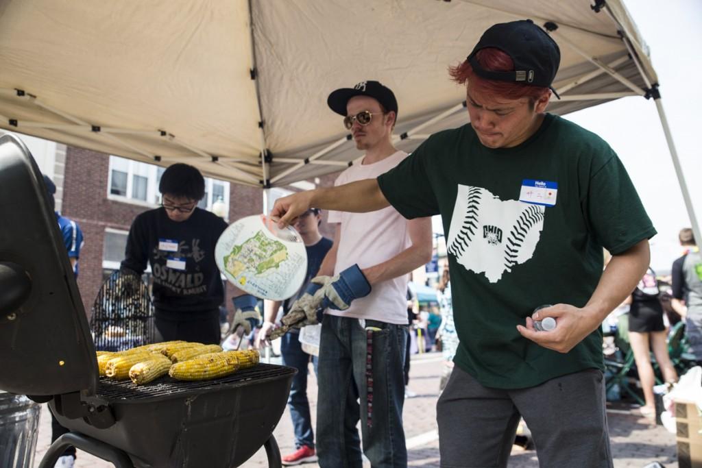 Subaru Hamaoka of Japan, right, bakes corn with Dakota Williams of Virginia, middle. and Akihisa Kawai of Japan, left on the International Week Street Fair on the Court Street in Athens, Ohio, on April. 15, 2017. (Wangyuxuan Xu/WOUB)