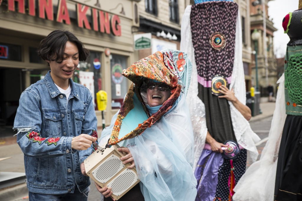 Jie Mei, left, who comes from China, plays Patty Mitchell's music box, right, on the International Week Street Fair on the Court Street in Athens, Ohio, on April. 15, 2017.  (Wangyuxuan Xu/WOUB)