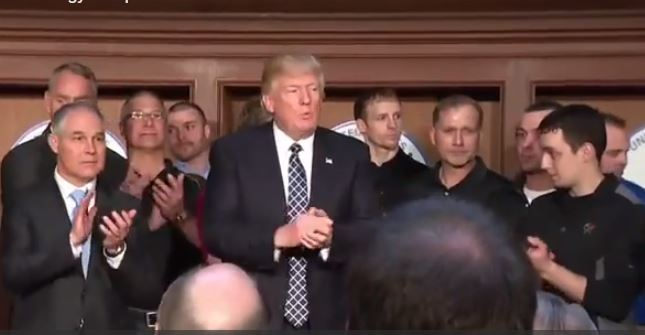Coal miners flanked President Trump as he signed the executive order undoing the Clean Power Plan. (From White House video)