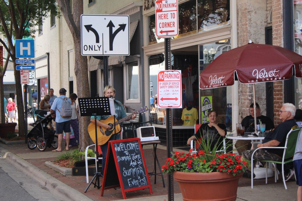 A street musician performs for a number of Lancaster Festival Artwalk attendees passing by. (WOUB/Emily Votaw)