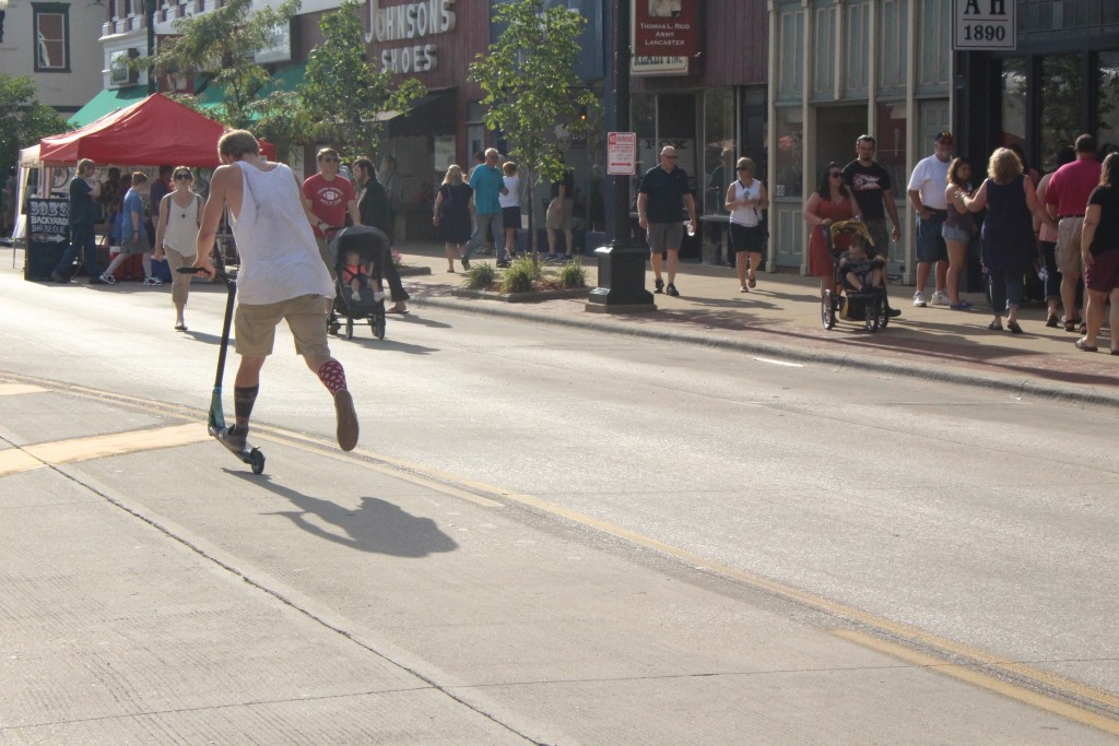 A young man scoots with great enthusiasm through the 2017 Lancaster Festival Artwalk. (WOUB/Emily Votaw)