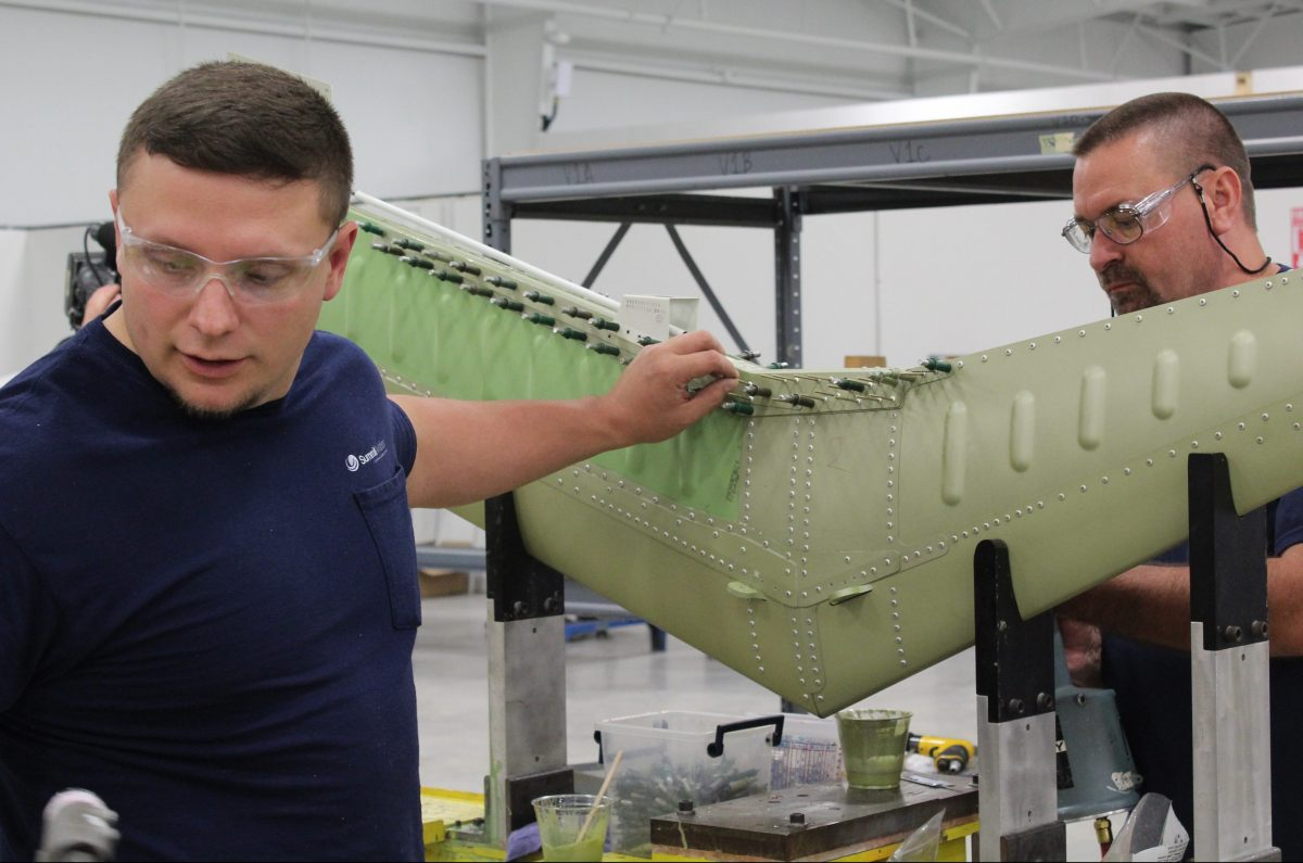 Employees work on a wing stabilizer part, one of Summit's main products. (Becca Schimmel/ Ohio Valley ReSource)