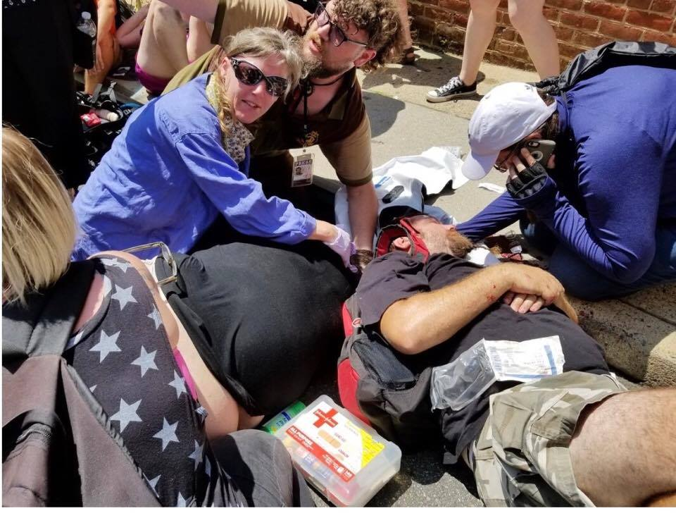 Bill Burke, second from right, gets medical attention after a car drove into a crowd of protesters in Charlottesville, Virginia. Next to him on the ground, in black, is Heather Heyer, who died in the attack.  Photo courtesy of Annie Jeffers Burke