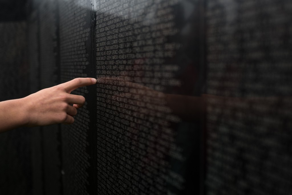 """A student from Crooksville Elementary touches a name on """"The Wall That Heals"""". (Nickolas Oatley/WOUB)"""