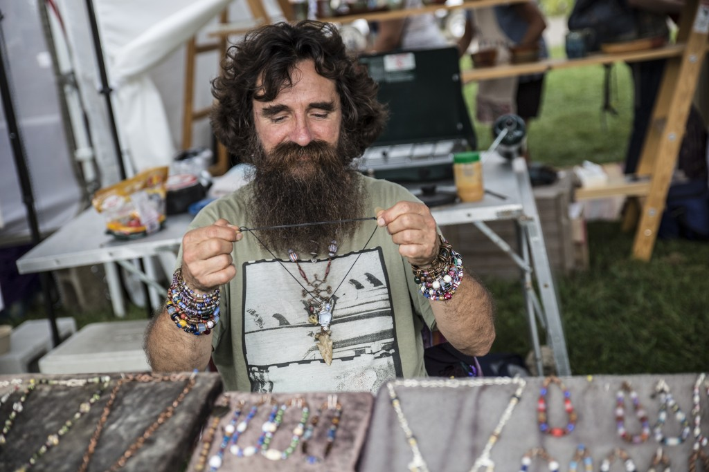 Rob Kola, a local jeweler, laces his handmade necklace at the Paw Paw Festival in Albany, Ohio on Sep. 16, 2017.(Wangyuxuan Xu/WOUB)