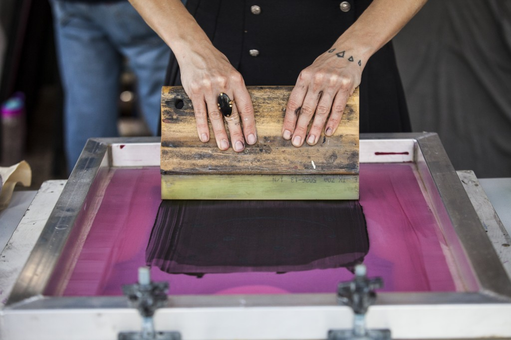Jaime Lewis of Paper Circle does silk screen printing on T-shirt in Paw Paw Festival in Albany, Ohio on Sep.16, 2017. (Wangyuxuan Xu/WOUB)