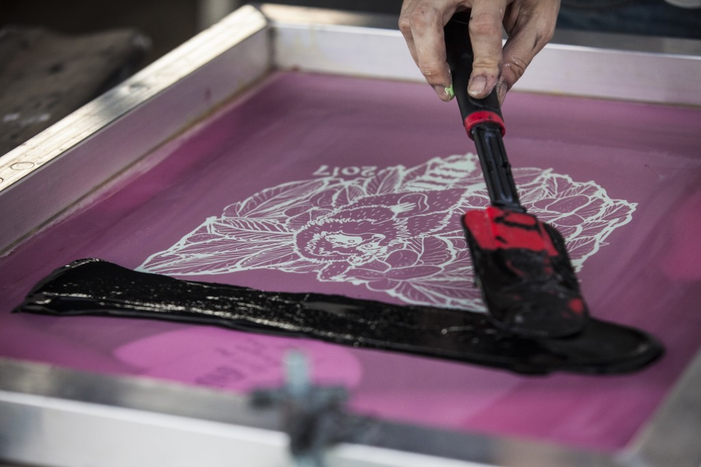 Jaime Whitlock of Paper Circle does silk screen printing on a T-shirt at the Paw Paw Festival in Albany, Ohio on Sep.16, 2017. (Wangyuxuan Xu/WOUB)