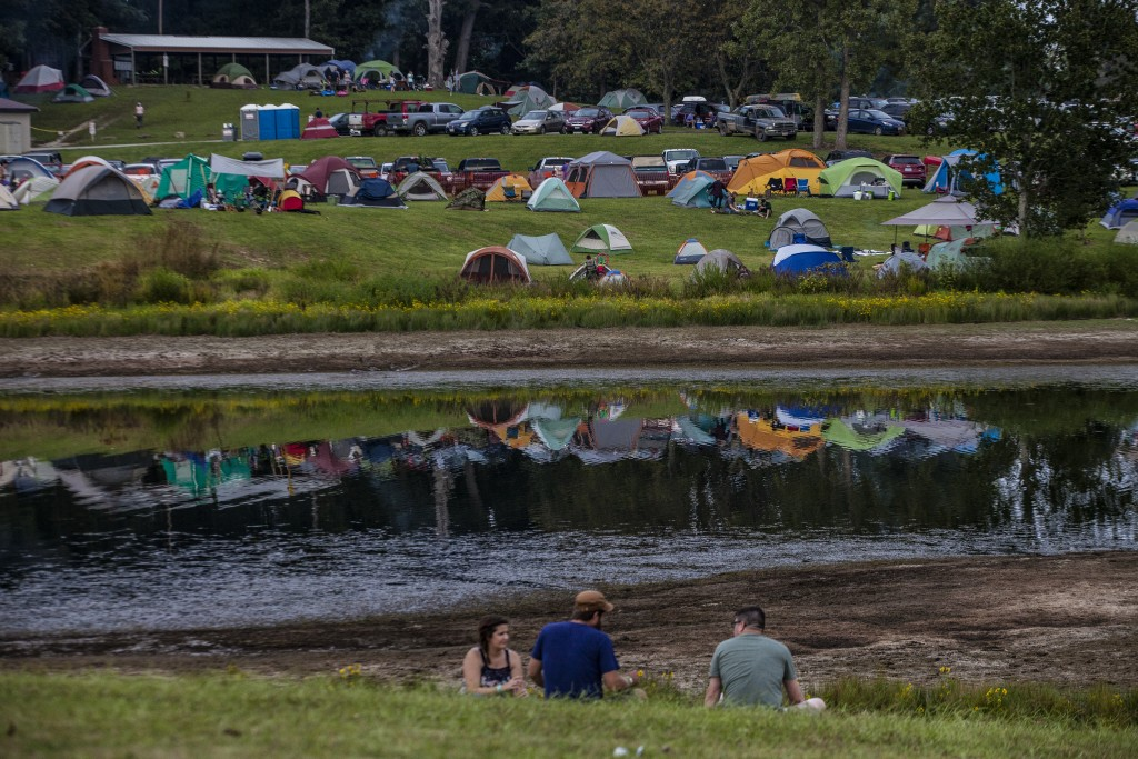 Paw Paw Festival attendees sit on a hill that looks out over the tents set up for the festivities in Albany, Ohio on Sep. 16, 2017. (Wangyuxuan Xu/WOUB)