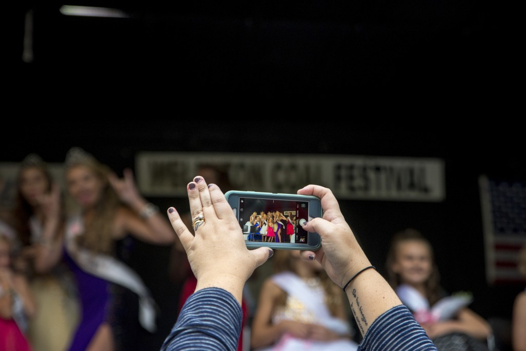 Kristen Smith, mother of contestant Shelby Smith, takes a photo of the finalists of the pageant with her cell phone. (Austin Janning/WOUB)
