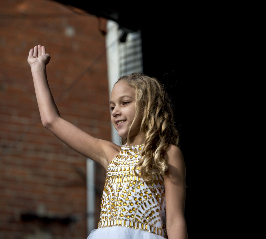 Emma Figgins, a contestant in the Little Miss Coal Festival Queen Contest, waves to the crowd as she walks on stage. (Austin Janning/WOUB)