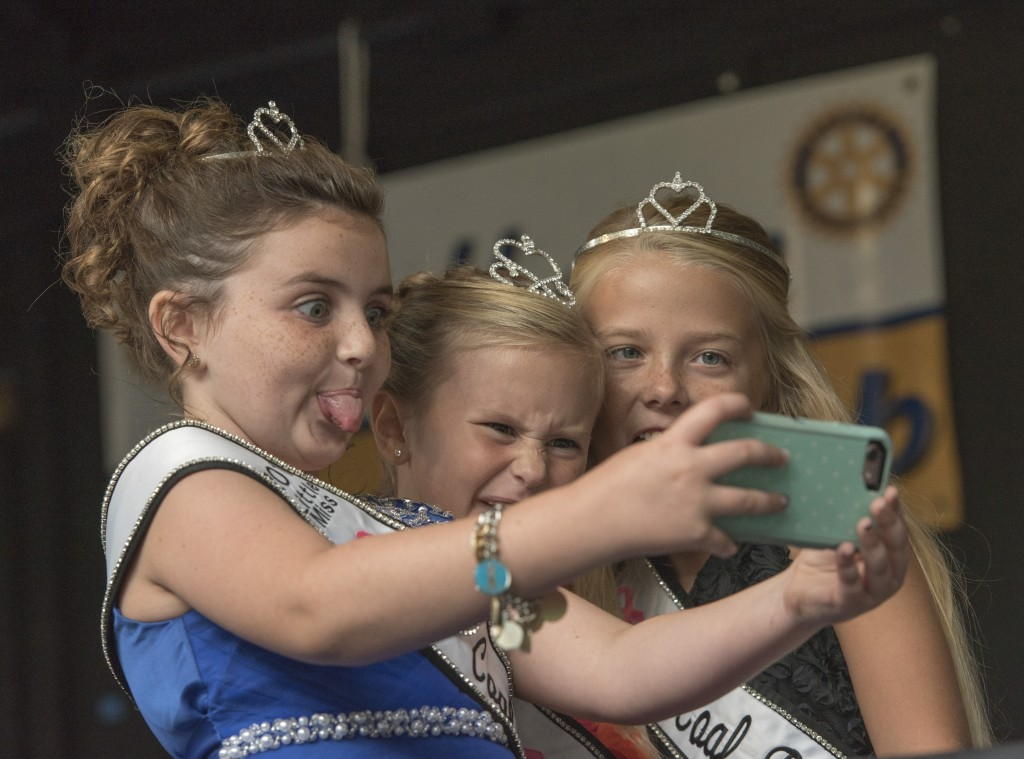 (From left to right) Shelby Smith, Ella Hitchinson, and Lindsey McCormick, take a selfie together at the Little Miss Coal Festival Queen Contest. (Austin Janning/WOUB)