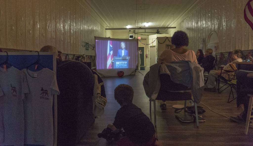 Attendees at the Athens County Democratic Party gubernatorial debate watch party spectate the candidates for governor answering questions on a projector screen.(Austin Janning/WOUB)