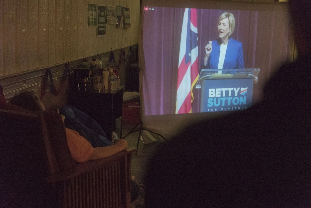 An attendee at the Athens County Democratic Party gubernatorial debate watch party spectates Betty Sutton, a candidate for governor answering a question on a projector screen. (Austin Janning/WOUB)
