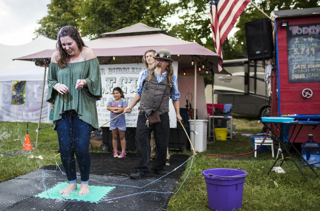 Ally Bucher reacts under a popped bubble created by Professor Bubblemaker at The Pawpaw Festival on Saturday, September 16, 2017. (Erin Clark/WOUB)