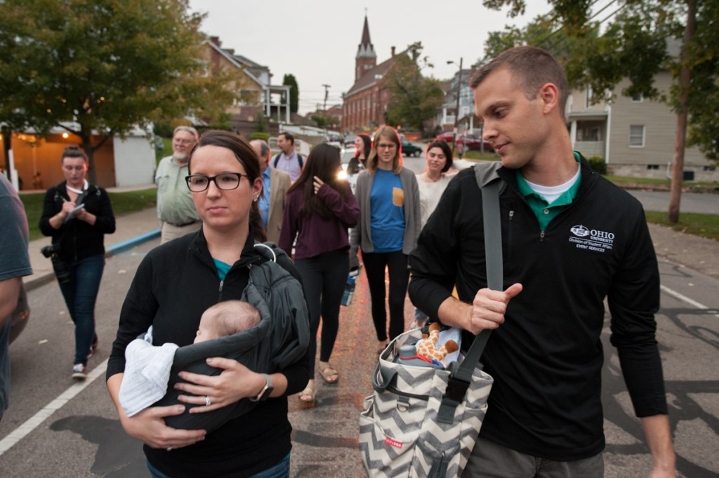 Keylee Wilkof holds her daughter, Aurelia, as she and her husband, Evan Wilkof (right) make their way down Mill Street with the rest of the group. (Drake S. Withers / WOUB)
