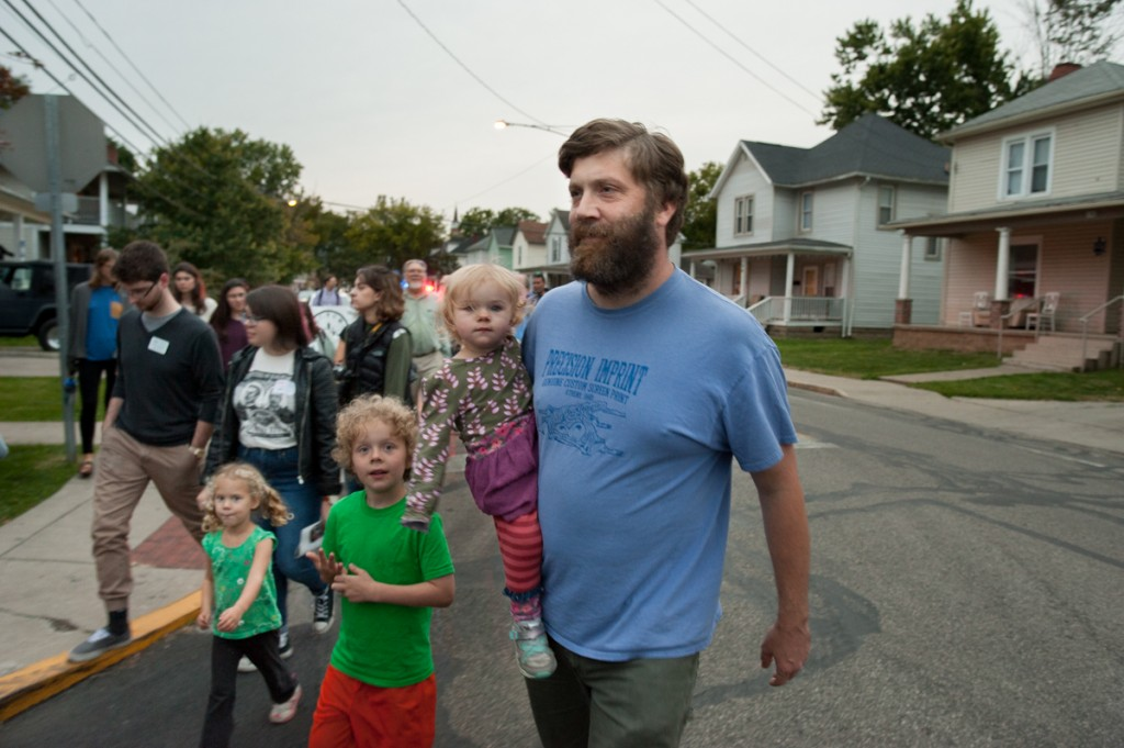 Jim Walker carries his daughter, Cerys Walker, with his son Seth Walker beside him during the Interfaith Peace Walk on Monday, Sept. 11, 2017. (Drake S. Withers / WOUB)