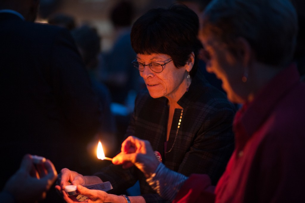 Anne Sparks and other participants in the Peace Walk share matches to light candles during a candlelight vigil. (Drake S. Withers / WOUB)