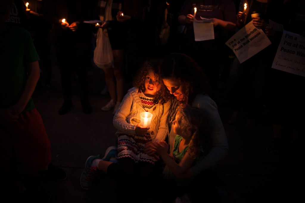 Rachel Siegel holds her daughters, Talia and Evelyn Siegel, as they sing hymns during the candlelight vigil at the close of the Interfaith Peace Walk on Monday, Sept. 11, 2017. (Drake S. Withers / WOUB)