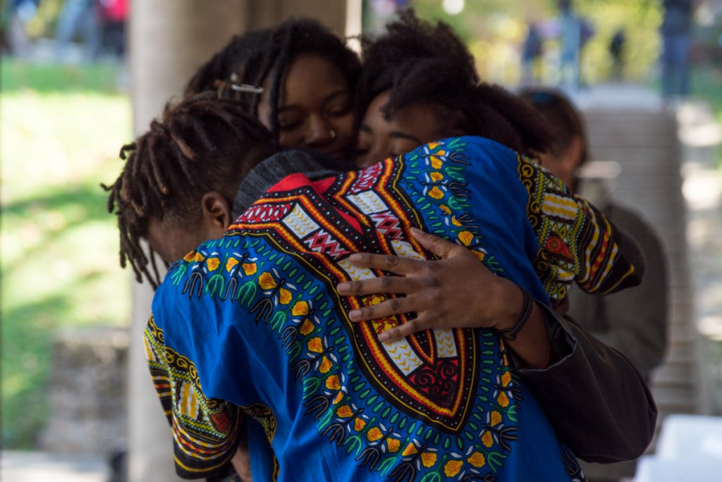 Prince Shakur, Joana Watson and Jazzmine Zabriel embrace each other after the National Anthem. (Nickolas Oatley/WOUB)