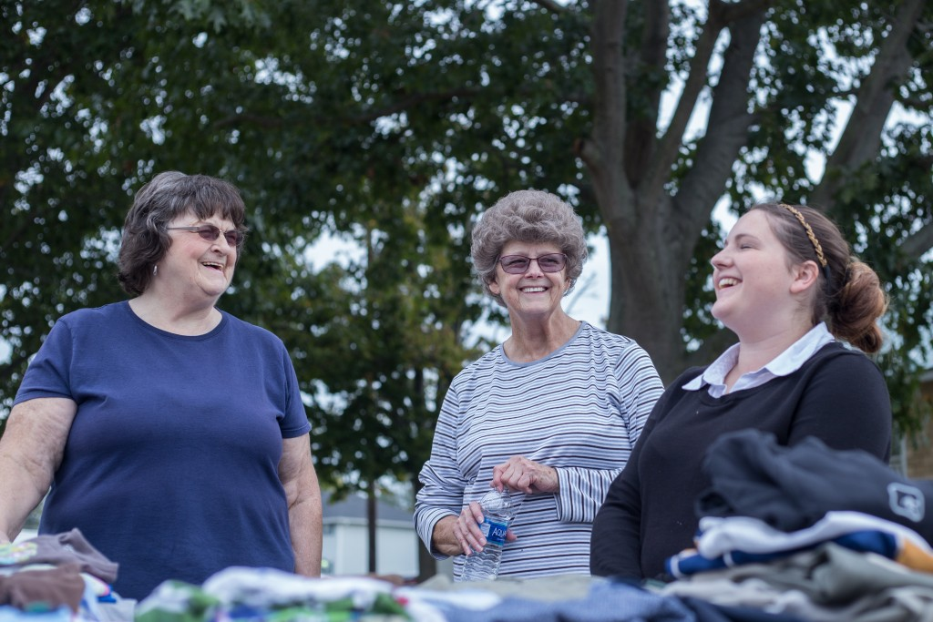 Barbara Collins (left), Charlotte Pedigo and Kim Roberts (right) talk and all help fold the clothes they collected through The Plains Church of the Nazarene for the Athens Area Stand Down on October 6, 2017, at the Athens County Fairgrounds. (HANNAH SCHROEDER | FOR WOUB)