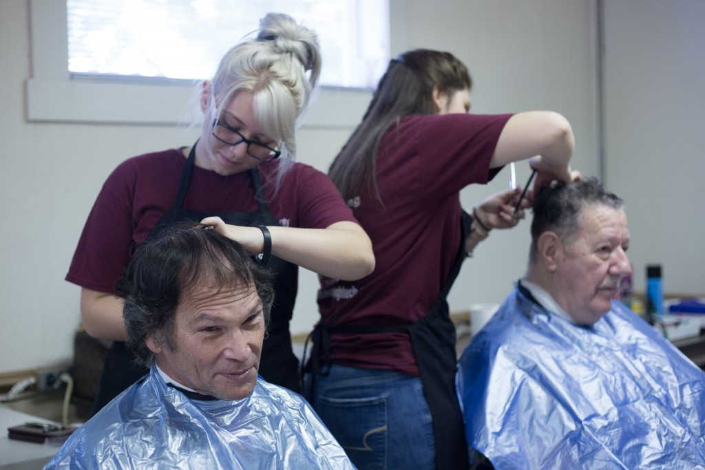 Kim Hilliard (left) and George Bice (right) get their hair cut by Madison Touvell (left) and Laiken Hamilton (right) who is a senior studying at the Tri County Career Center. Instructor Rebecca Dicken brought high school seniors from her class to give free haircuts to the attendees at the Athens Area Stand Down on October 6, 2017. (HANNAH SCHROEDER | FOR WOUB)