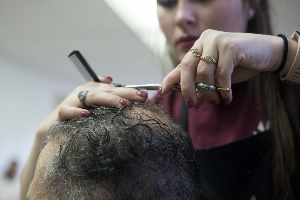 George Bice gets his hair cut by Laiken Hamilton who is a senior studying at the Tri County Career Center. Instructor Rebecca Dicken brought seniors in high school from her class to give free haircuts to the attendees at the Athens Area Stand Down on October 6, 2017. (HANNAH SCHROEDER | FOR WOUB)