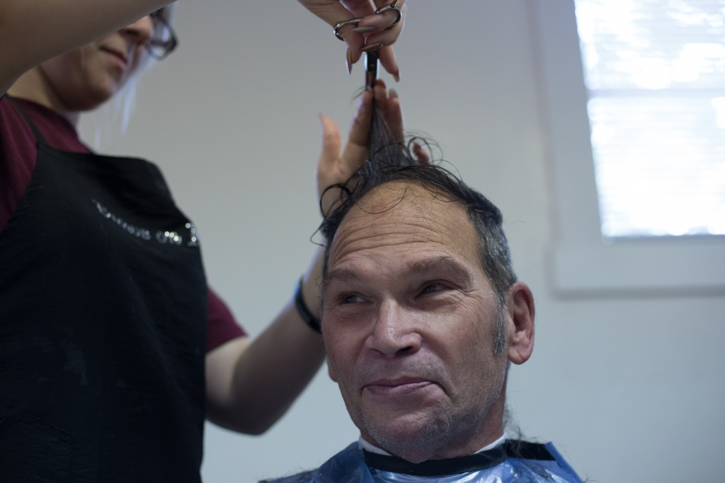 Kim Hilliard gets his hair cut by Madison Touvell who is a senior studying at the Tri County Career Center. Instructor Rebecca Dicken brought seniors in high school from her class to give free haircuts to the attendees at the Athens Area Stand Down on October 6, 2017. (HANNAH SCHROEDER | FOR WOUB)