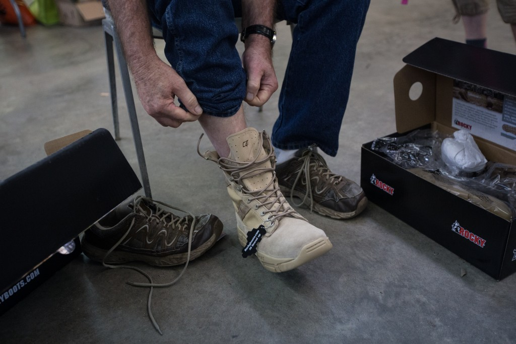 David Williams tries on a pair of Rocky boots to test their size. The Rocky brand donated over one hundred pairs of boots for the second year in a row to support this event and the Athens community. (HANNAH SCHROEDER | FOR WOUB)