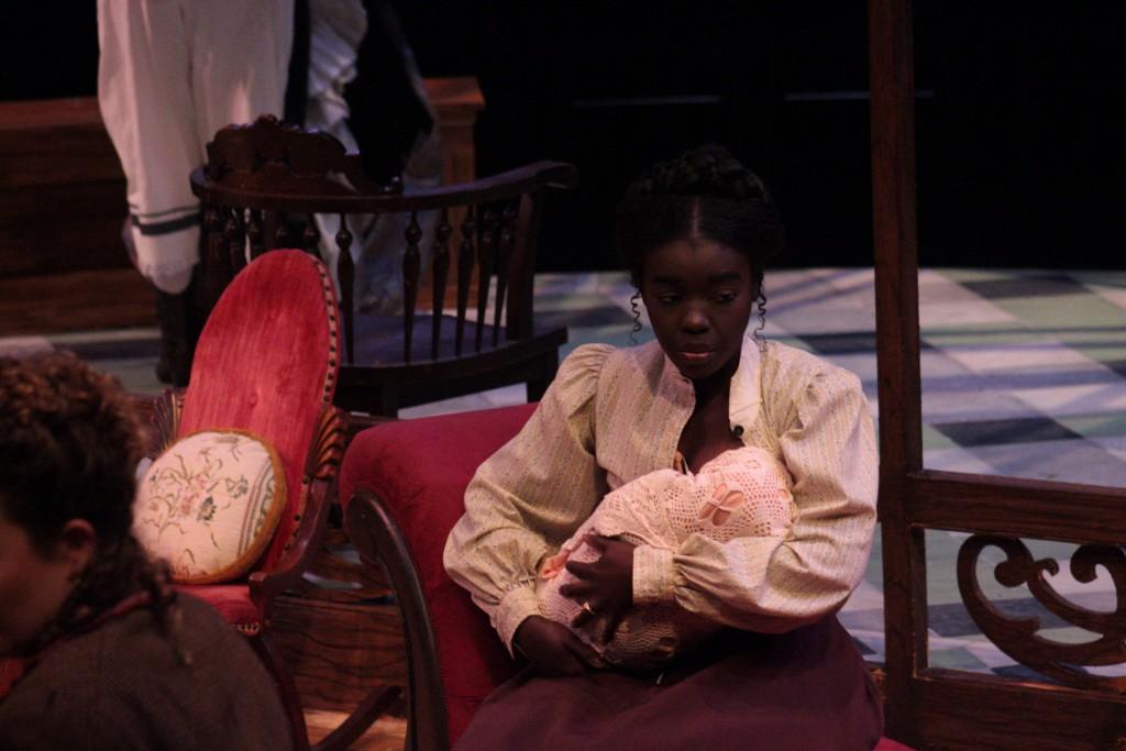 Simone Anderson (Elizabeth) cradles a baby. (Lisa Buch/WOUB Public Media)