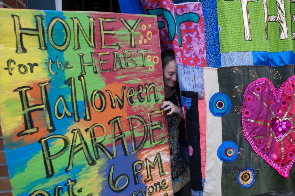 Patty Mitchell squeezes by a parade advertisement and a handmade quilt outside of Central Venue in Athens, Ohio, on October 24, 2017.   (Michael Johnson/WOUB)