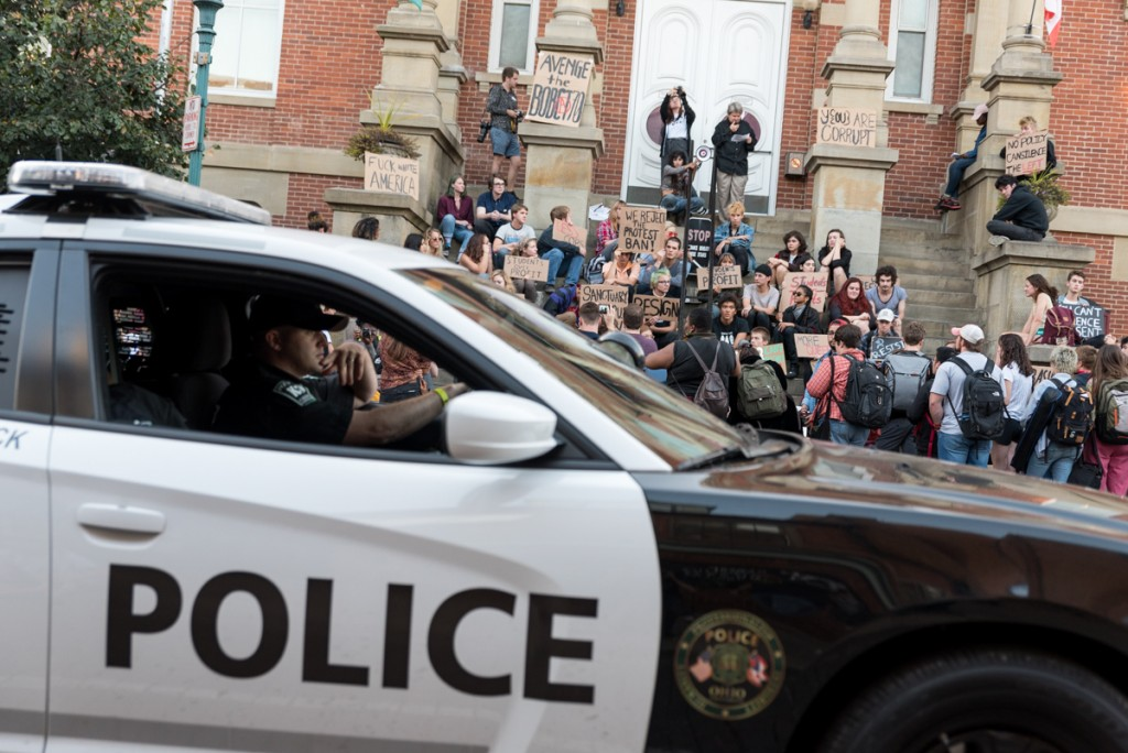 An Ohio University police cruiser passes the protest taking place on the footsteps of Athens Court House. (Nickolas Oatley/WOUB)