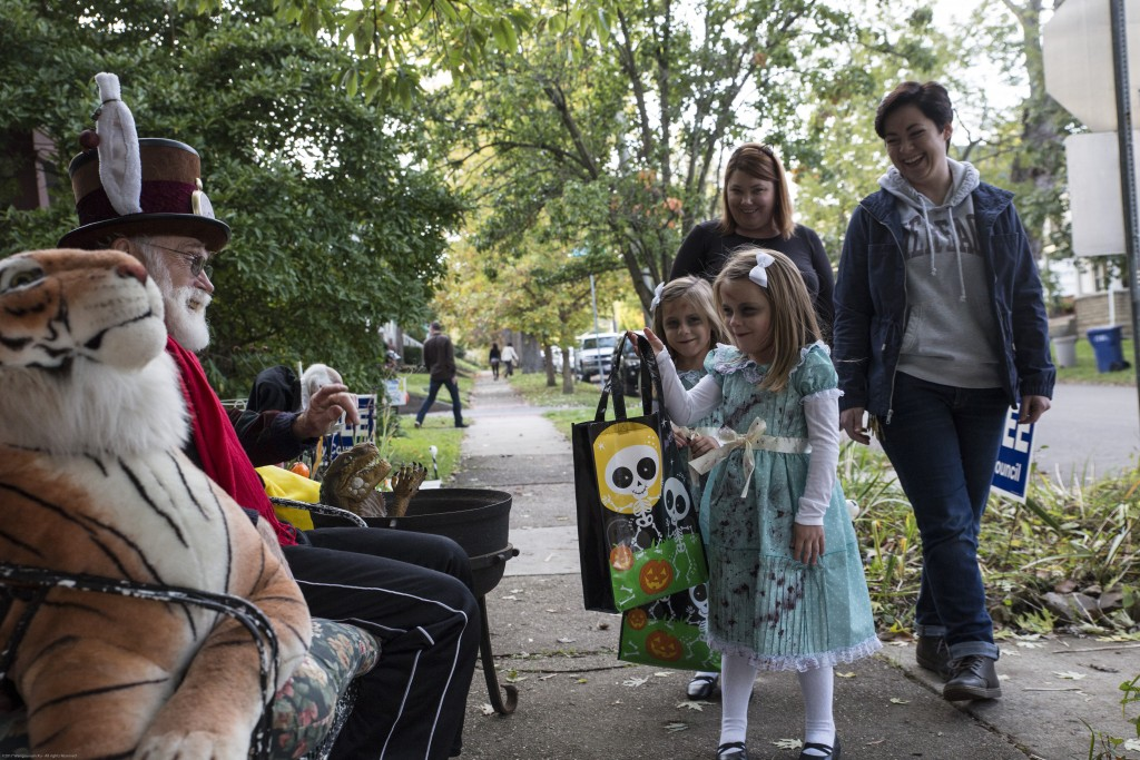 Pat McGee (left) who dresses as the white rabbit in Alice's adventure in wonderland, says hello to the passing by twin sisters, Jenna Trout-Wright and Medison Trout-Wright, Crystal and Heather's 5-year-old daughters in Athens, Ohio on October 26, 2017 (Wangyuxuan Xu/ WOUB)