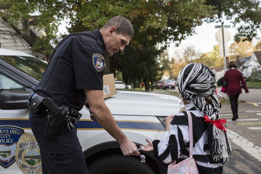 The police officer Andy Foster hands out candy to Norah Warmke, Jackie Warmke and Daniel Warmke's 4-year-old girl, on the crossroad in Athens, Ohio on Oct. 26, 2017. (Wangyuxuan Xu/ WOUB)