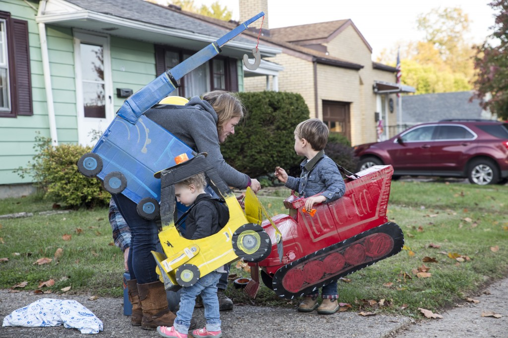 Vince Francis and Timaire Francis helps their son, Stan Francis, 4, and Gus Francis, 2, tape their costume in Athens, Ohio on Oct. 26, 2017. (Wangyuxuan Xu/ WOUB)