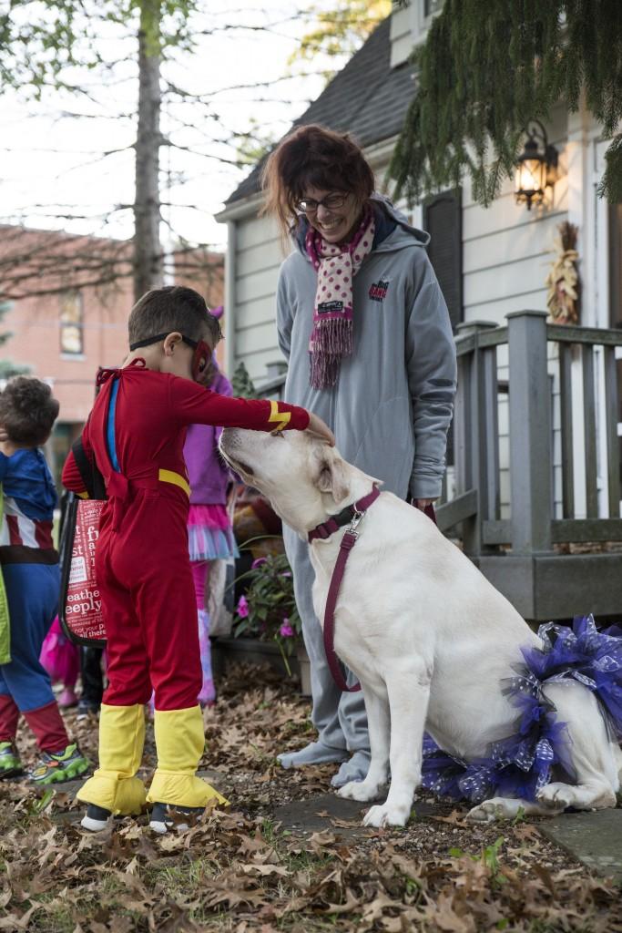 The flash, Silas Aftabizadeh, Shireen Aftabizadeh's 5-year-old boy, pats Julie Nuzum's dog, Fu, before he trick-or treats in Athens, Ohio on Oct, 26, 2017. (Wangyuxuan Xu/ WOUB)