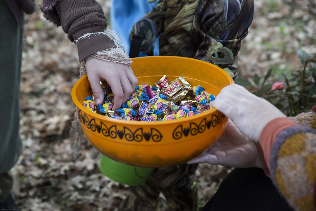 """Kid grabs the candy from Cathy Baker while saying the """"Trick-or-treat""""  in Athens, Ohio on Oct, 26, 2017. (Wangyuxuan Xu/ WOUB)"""
