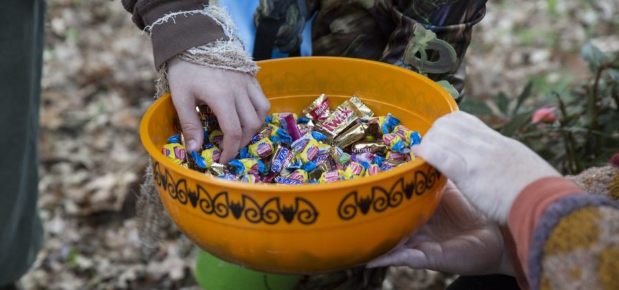 """Kid grabs candy from Cathy Baker while saying """"Trick-or-treat"""" in Athens, Ohio on Oct, 26, 2017."""